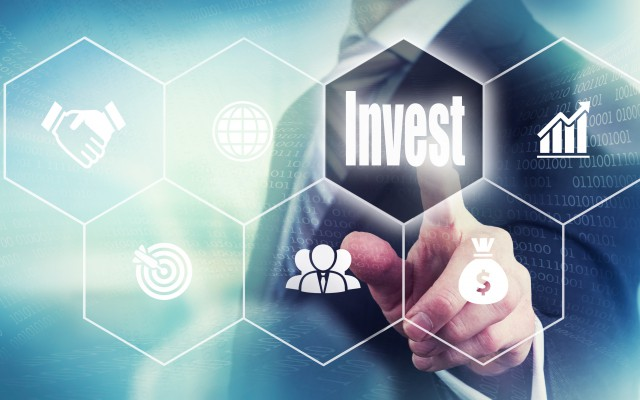 Businessman pressing an Invest concept button.